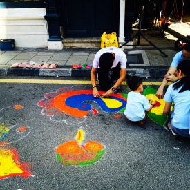 FAMILIES PUTTING RANGOLI FOR DEEPAVALI FESTIVAL